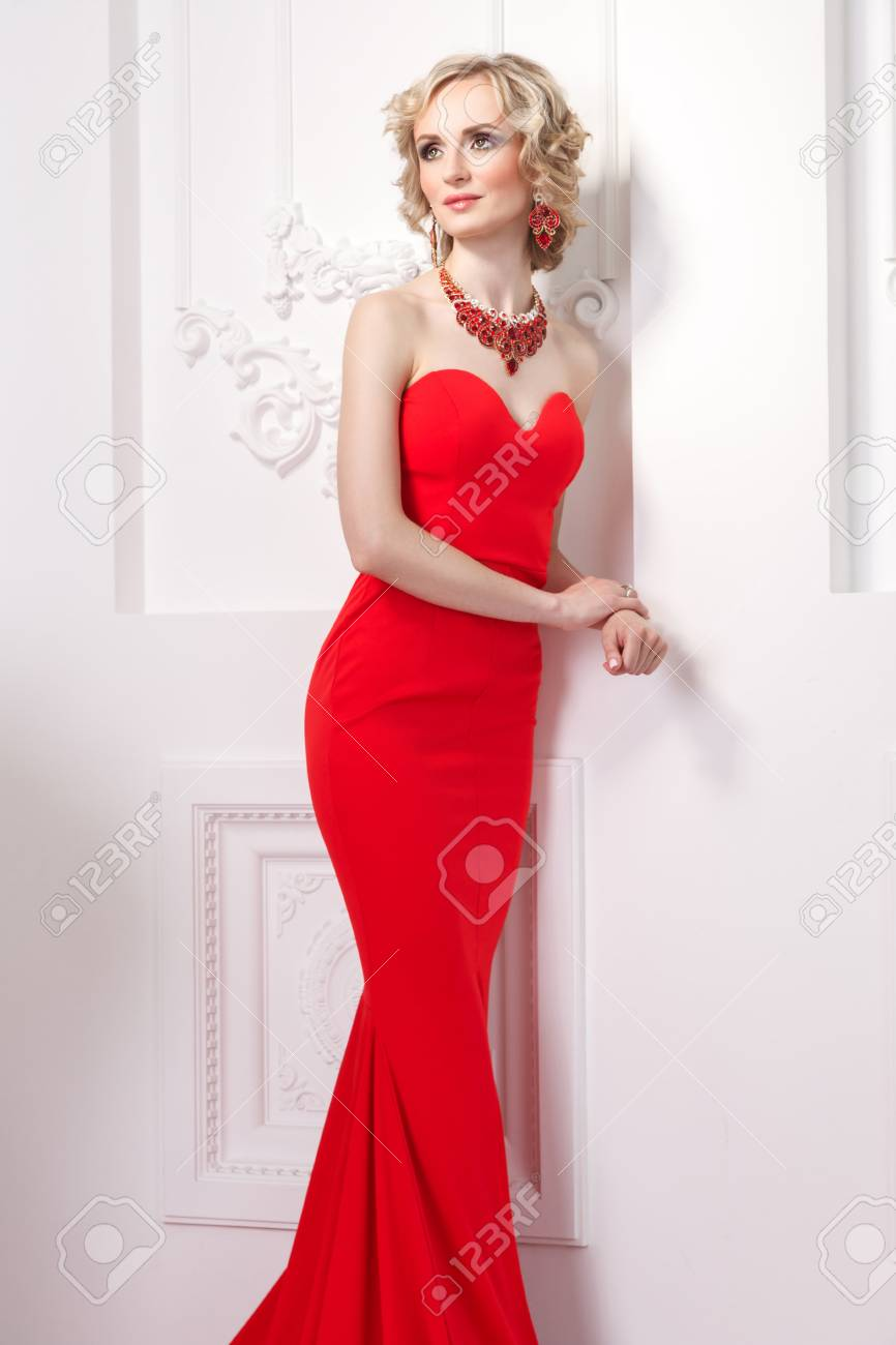 Fashion model in red dress, curly hairstyle and glamour jewelry
