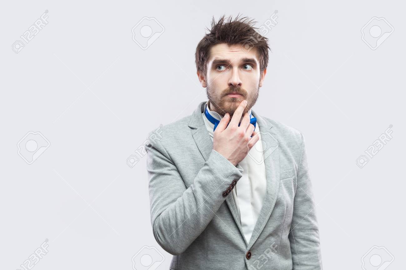 e205567b3c4a Portrait of doubtful handsome bearded man in casual grey suit and blue bow  tie standing touching