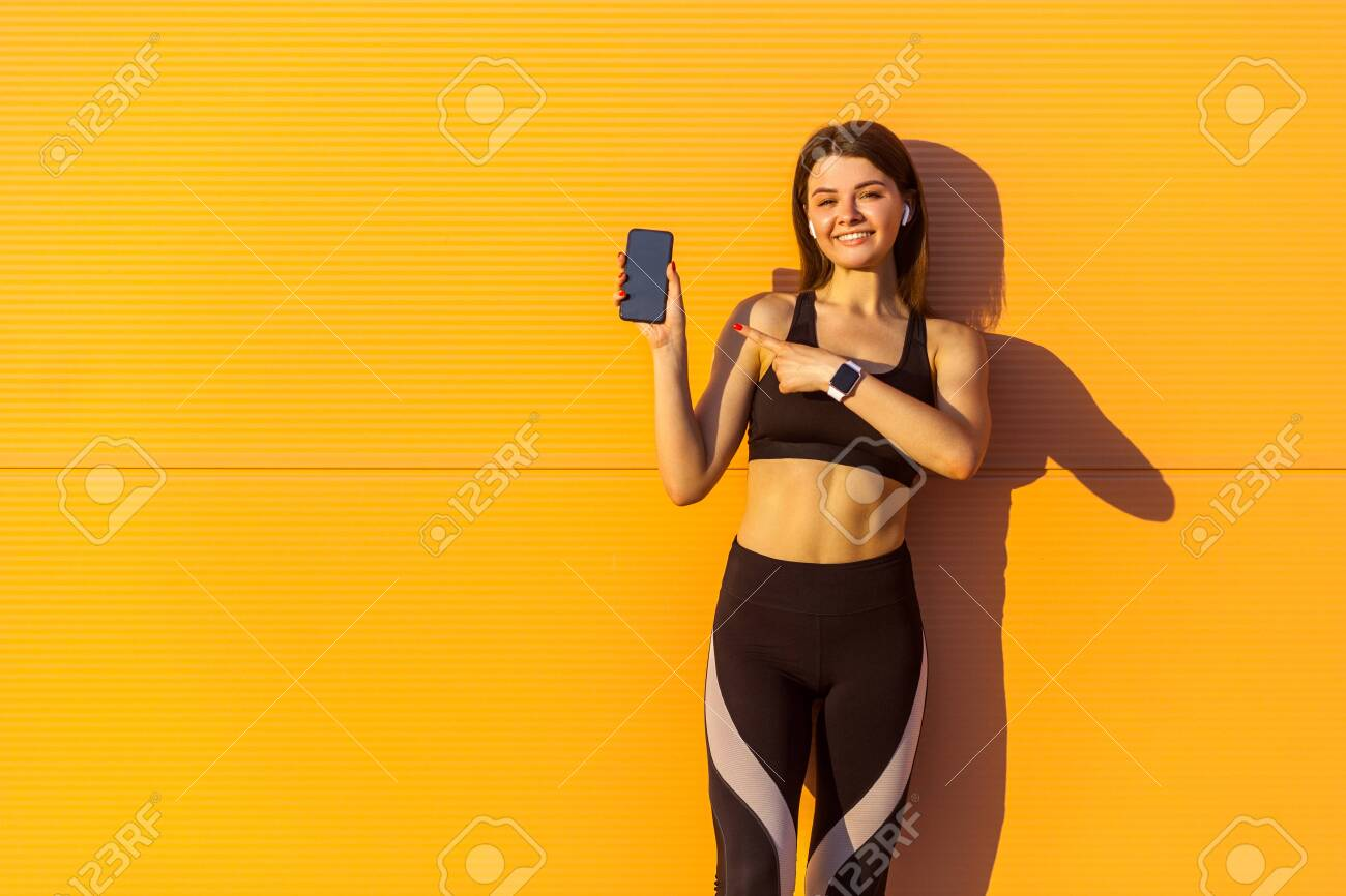 Young satisfied beautiful sporty woman in black sportwear standing near orange wall background and holding phone, pointing finger with toothy smile, looking at camera, outdoor on summer, sunshine - 126960011