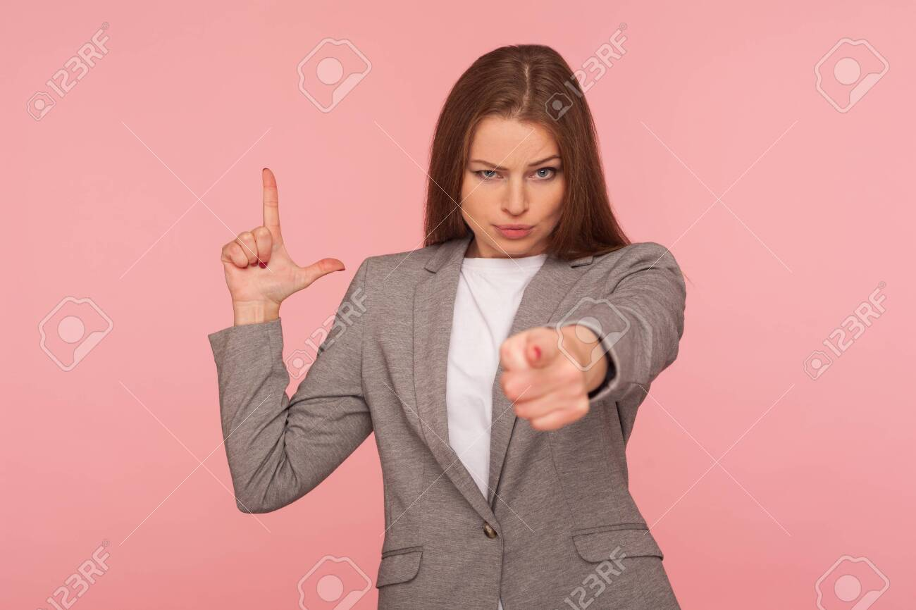 You are fired! Portrait of displeased young woman in business suit pointing to camera and making L sign with fingers, showing loser gesture, accusing for failure. studio shot, pink background - 148294384