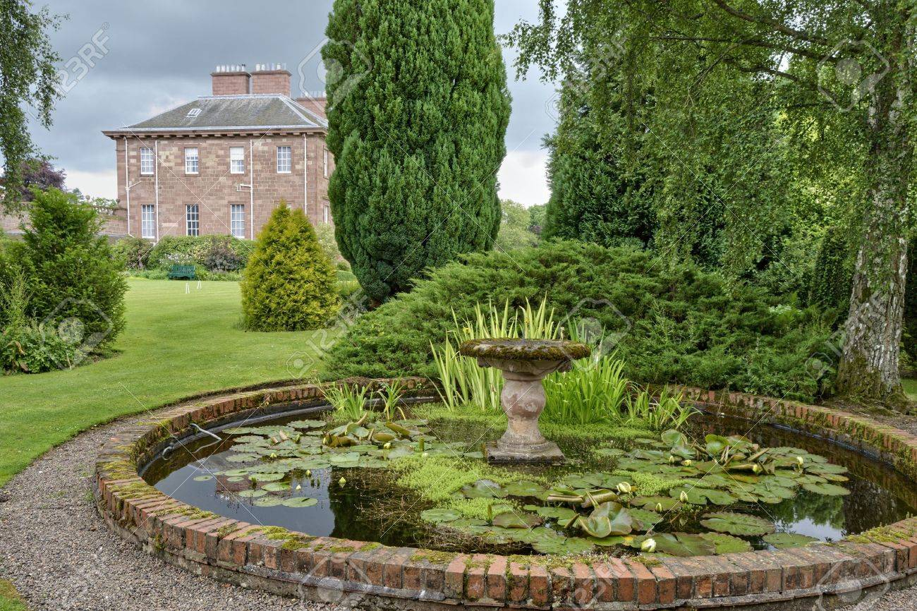 An ornamental pond in a country estate garden with a large  in the background Stock Photo - 3417176