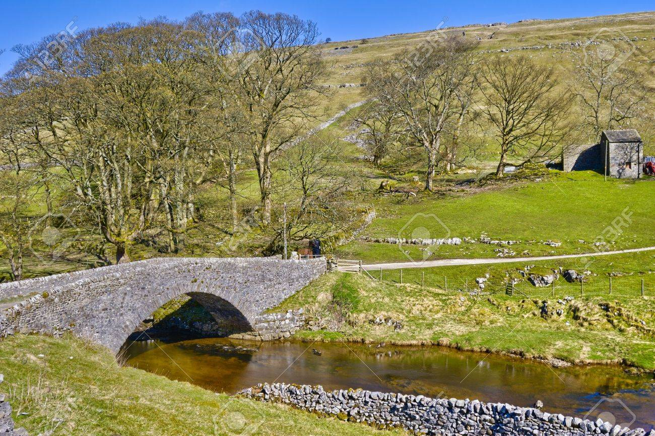 Scenic view of stone packhorse bridge over river Wharf with Yockenthwaite village in background, Wharfedale Valley, Yorkshire Dales, England. Stock Photo - 4888531
