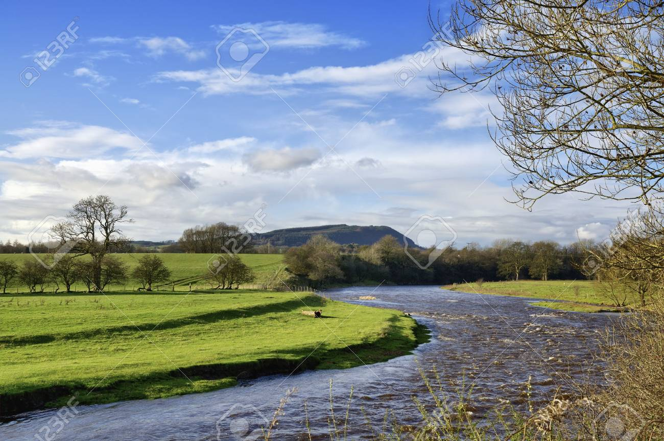 A view of the curving River Ribble wending its path through fields near Clitheroe, Lancashire, with Longridge Fell in the distance, on a sunny autumn day Stock Photo - 17462077