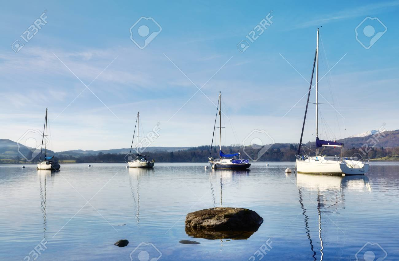Tranquil view of four boats moored peacefully on Lake Windermere, with a rock in the foreground, on a sunny winters morning in the English Lake District Stock Photo - 18517401