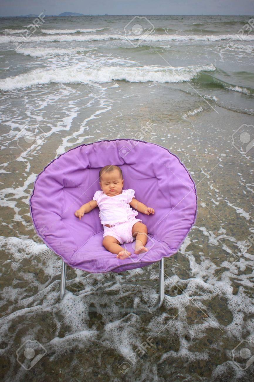 Baby Sitting On Round Chairs At Sea Beach Stock Photo, Picture And ...