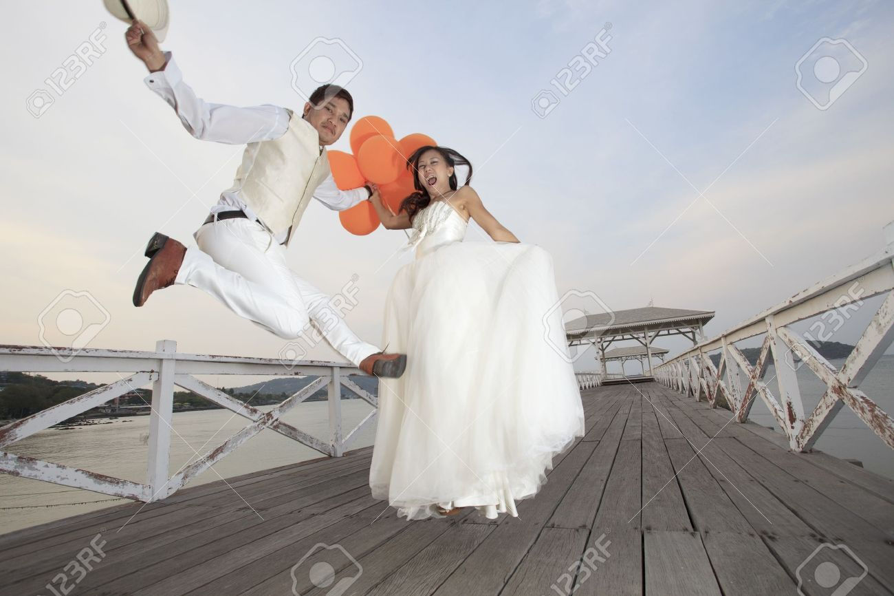 couple of groom and bride  in wedding suit  jumping with glad emotion on wood bridge  use for wedding and honey moon ceremony theme Stock Photo - 21069752