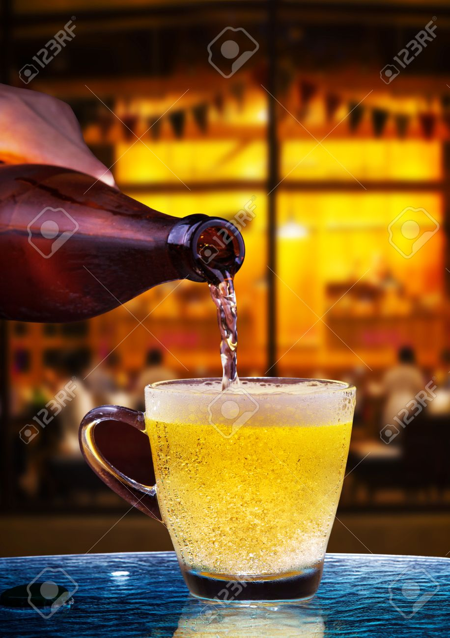 stock photo lager beer drain from bottle to glass on table with beautiful lighting of snack bar use for alcohol drinking beverage in adult pub bar and beautiful lighting