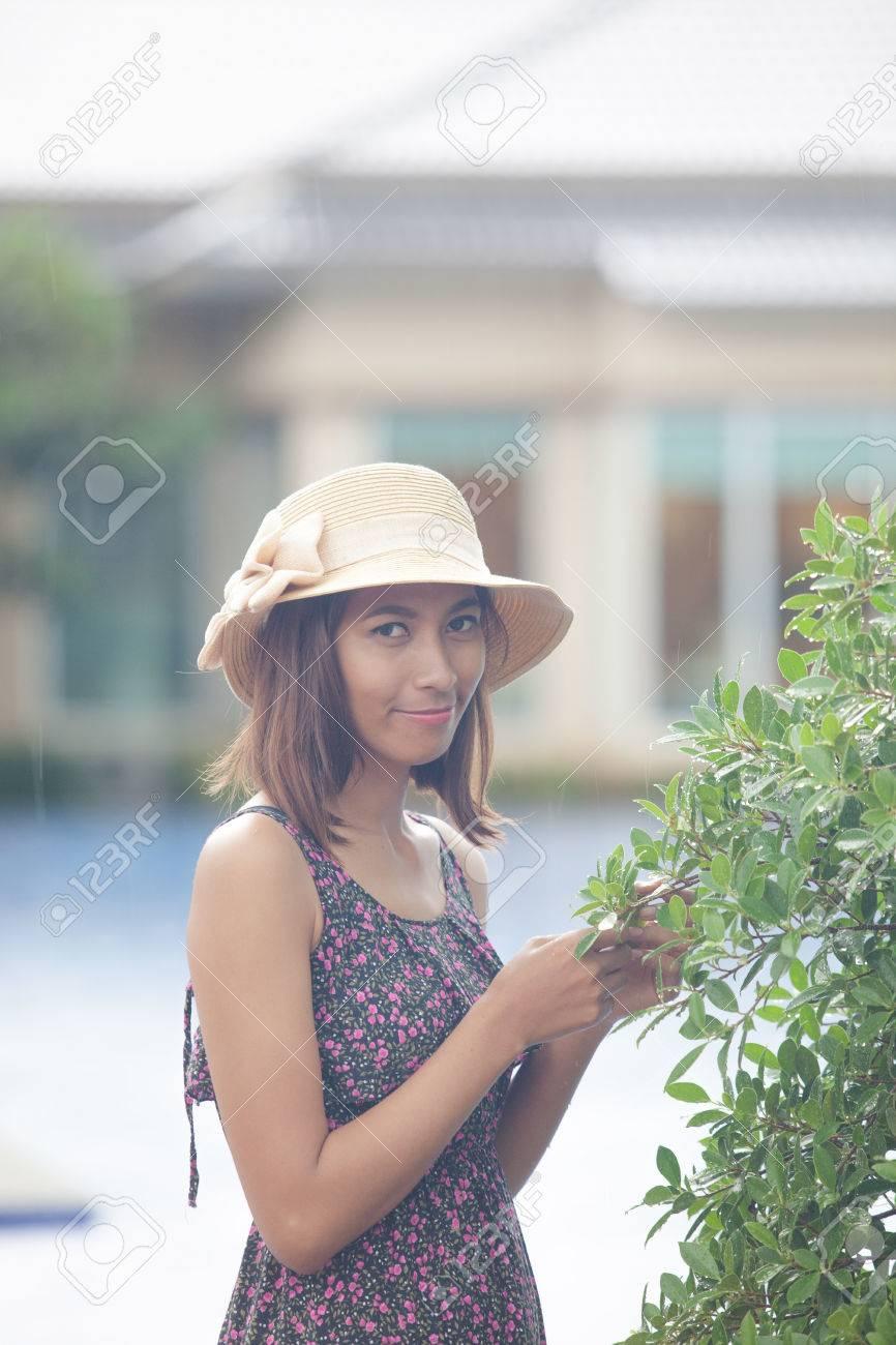 Foto de archivo - Retrato de la hermosa mujer asiática piel bronceada con  un vestido largo y sombrero de paja de pie en el parque de llover día con  la cara ... d581c6910ba