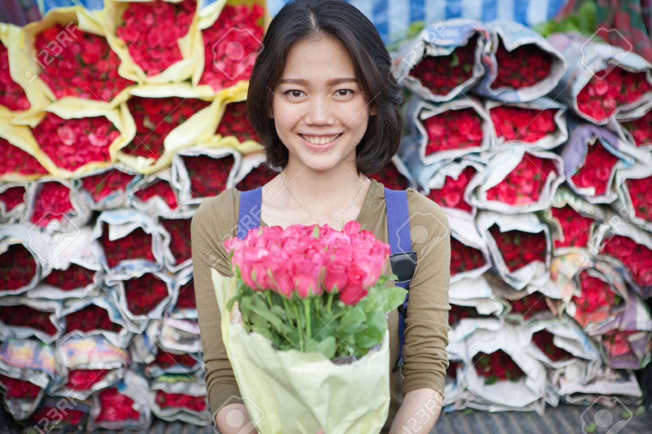 Smiling face of younger asian woman with pink roses flower bouquet smiling face of younger asian woman with pink roses flower bouquet in hand stock photo izmirmasajfo