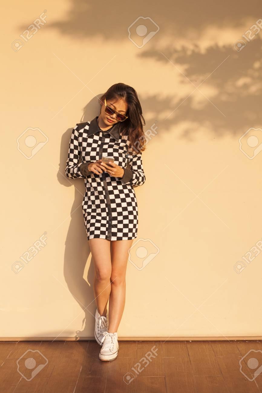 Joven Y Bella Mujer Inconformista Llevaba Lentes De Sol Y Leyendo Los Medios Sociales En El Teléfono Inteligente Contra Cálida Pared De Color Amarillo
