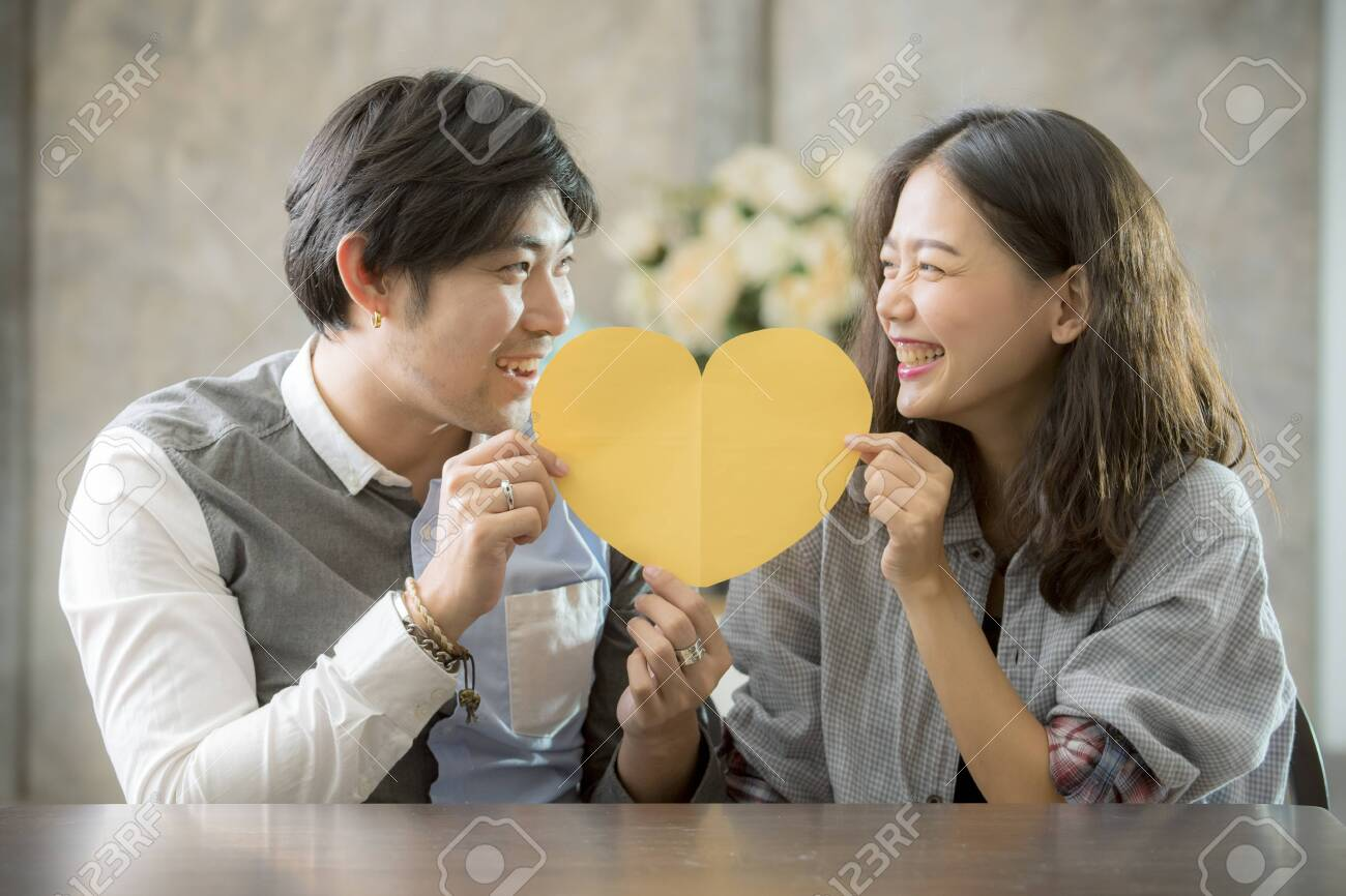 couples of asian man and woman holding heart shape paper cut with happiness emotion ,people love conceptual - 140824776