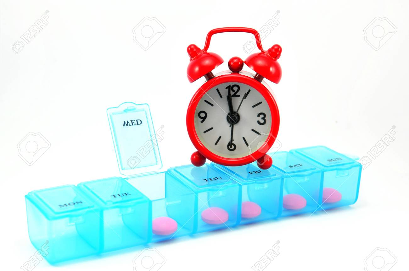 Dialy pill box and red clock on white blackground show medicine time concept Stock Photo - 13639186