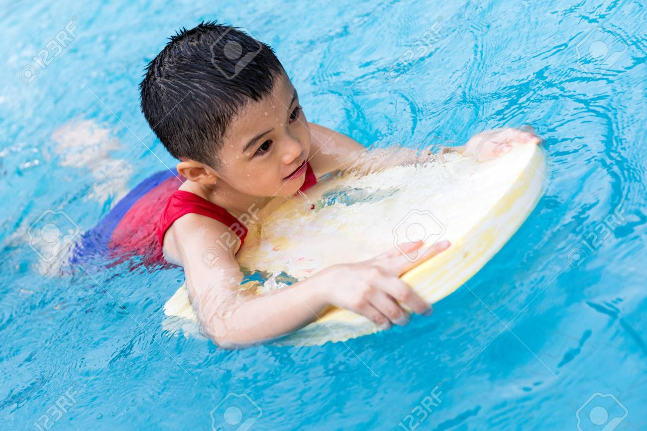 1f323113bf Asian Chinese Little Boy Swimming With Floating Board at Outdoor Swimming  Pool. Stock Photo -