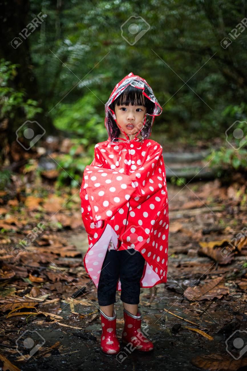 a7684afb7e Asiatisches chinesisches kleines Mädchen , das Regenmantel im tropischen  Regenwald allein trägt Standard-Bild -