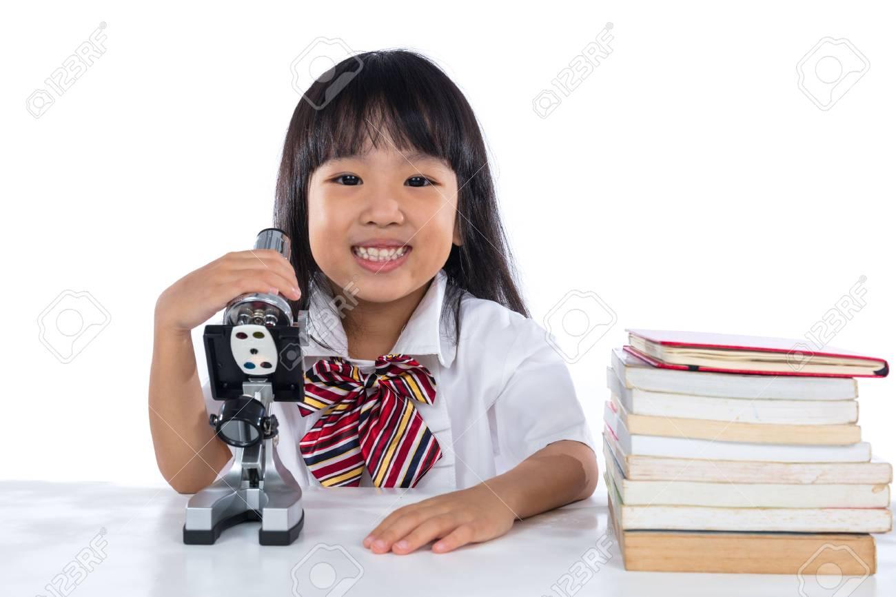 Glückliches asiatisches chinesisches kleines mädchen mit mikroskop