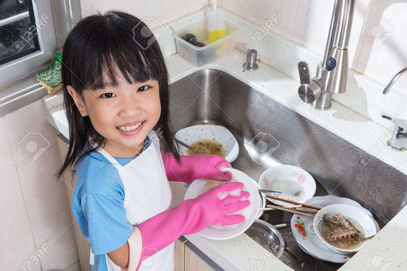 Asian Chinese Little Girl Washing Dishes In The Kitchen At Home Stock Photo    76076557