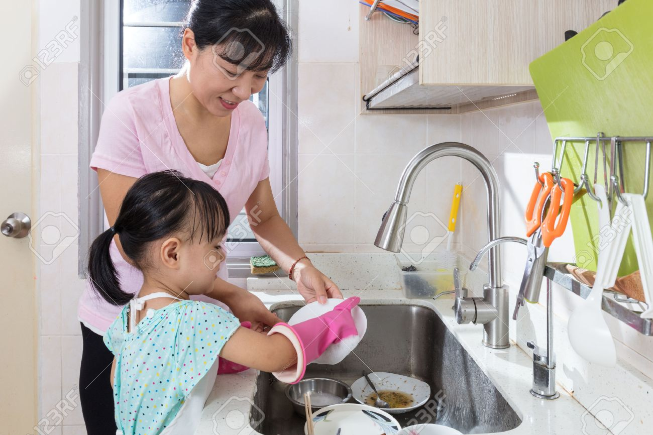 Asian Chinese Little Girl Helping Mother Washing Dishes In The Kitchen At  Home Stock Photo