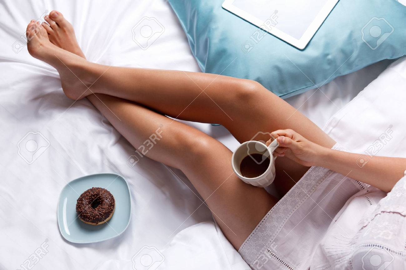 Woman having donut and coffee for breakfast in the bed Stock Photo - 46598261