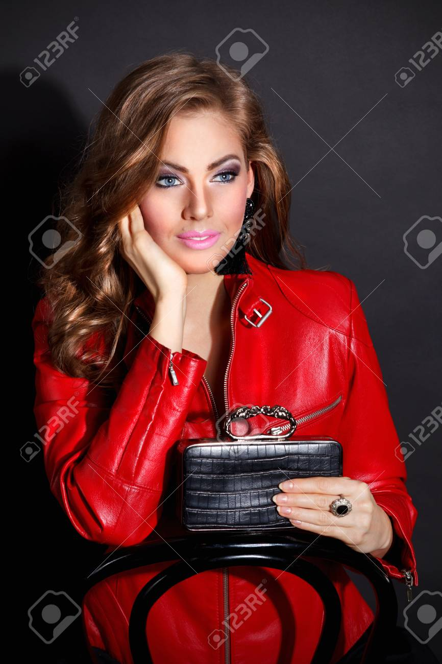Sexy woman posing with a bag in red leather jacket