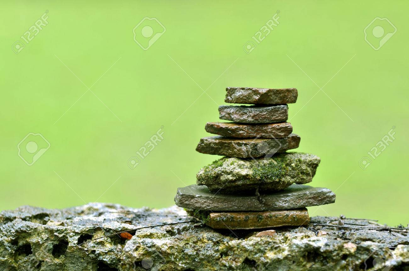 arranging stone on wet stone in forest zen style stock photo