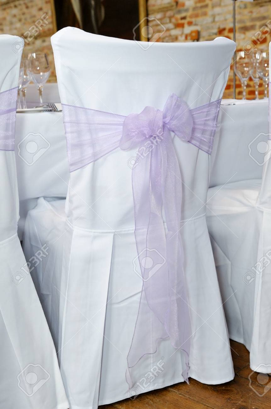 lilac ribbon in a bow on white chair cover at wedding reception