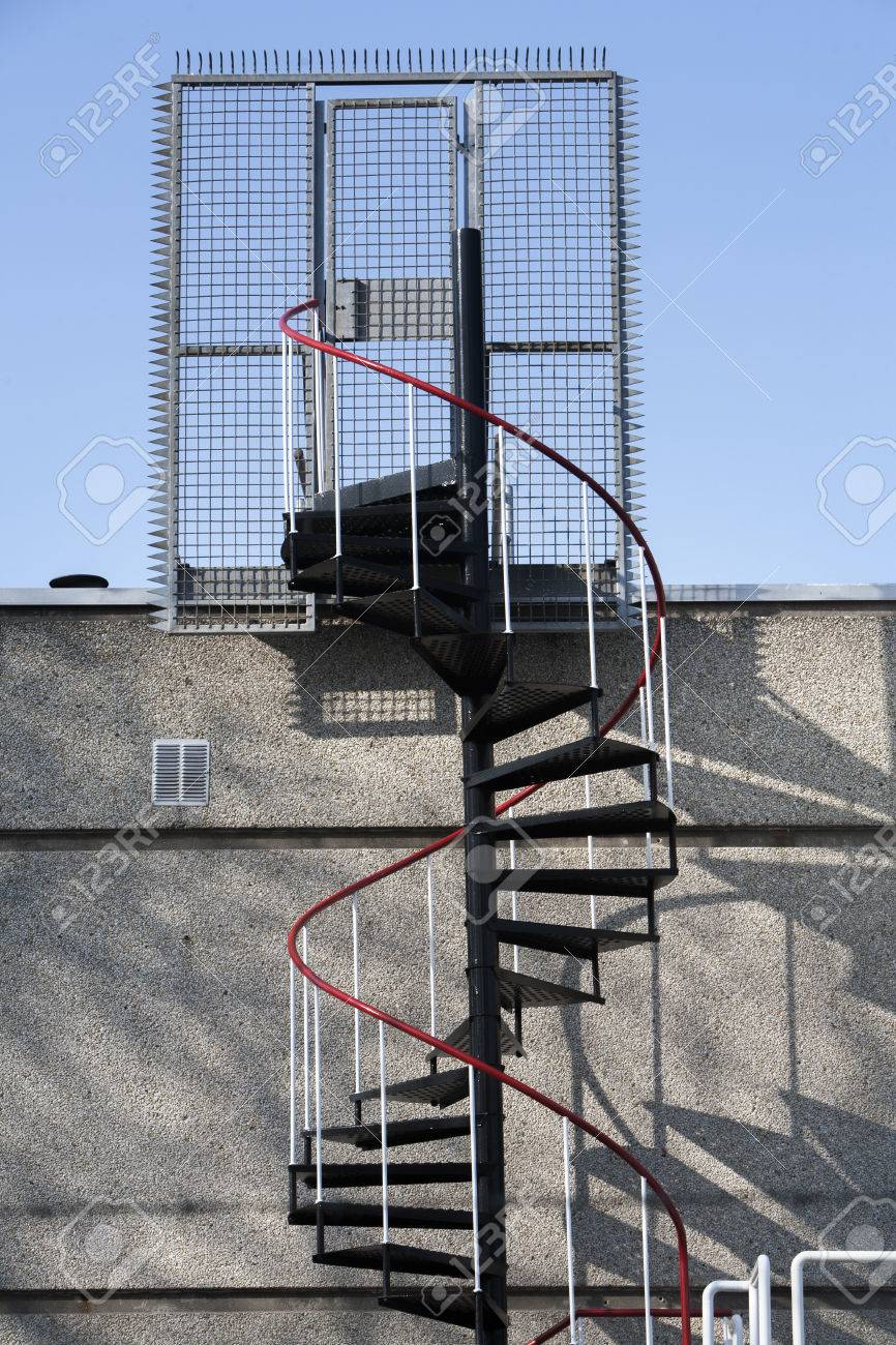 emergency exit with metal spiral staircase in the netherlands a fence and door with lock