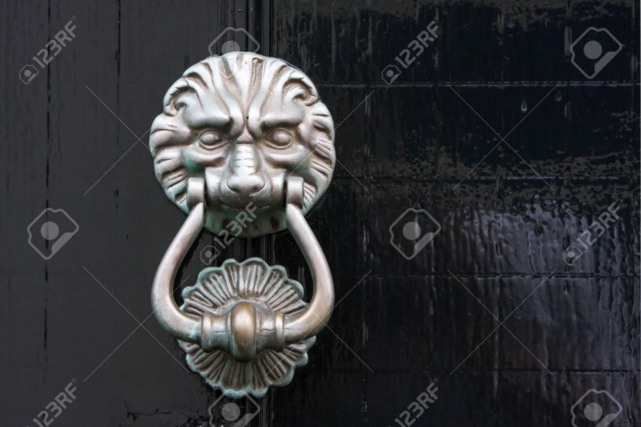 Antique lion door knocker on a black wooden door in the Netherlands Stock  Photo - 65828609 - Antique Lion Door Knocker On A Black Wooden Door In The Netherlands