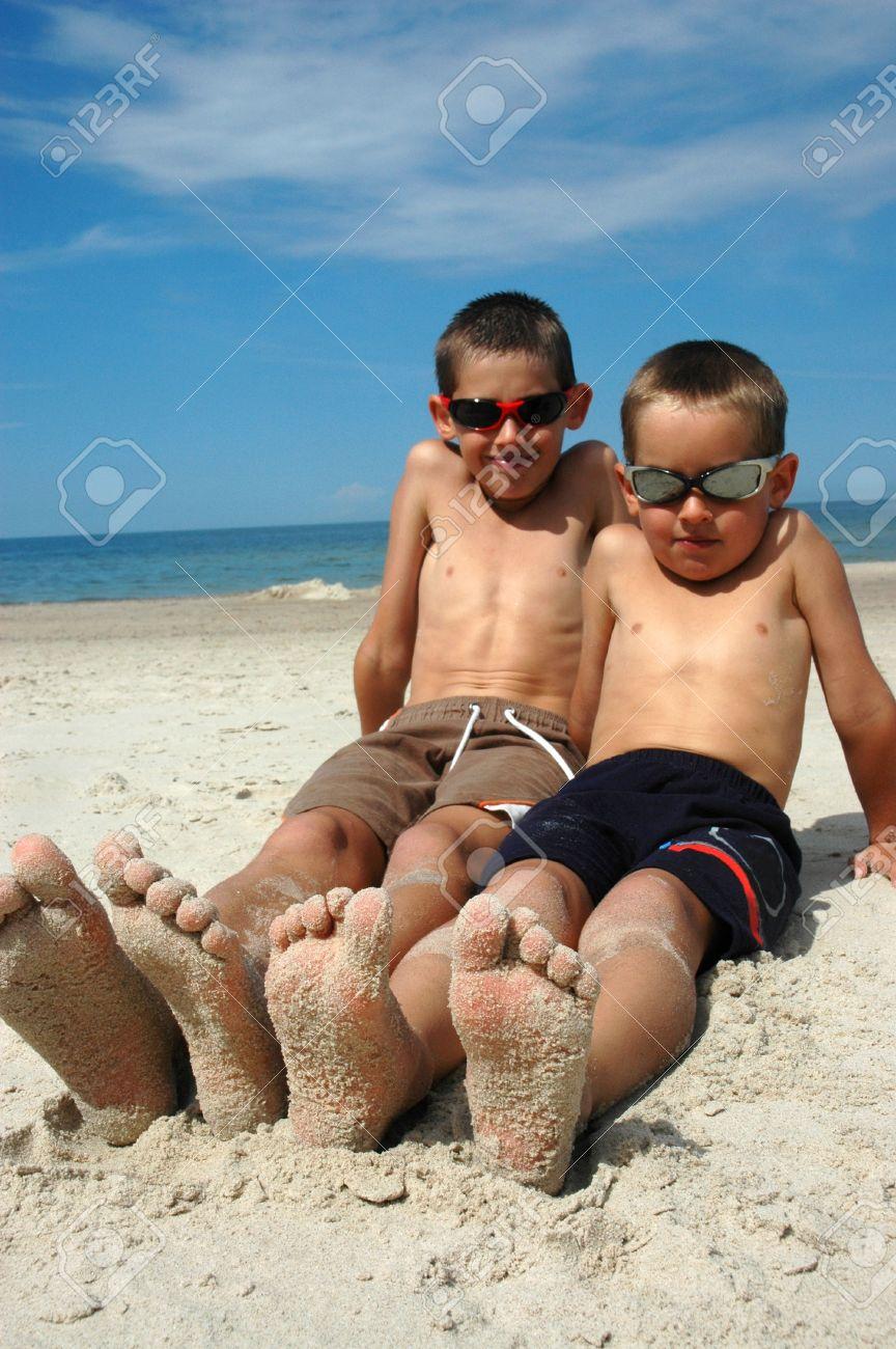 Two Boys Lying On The Beach St...
