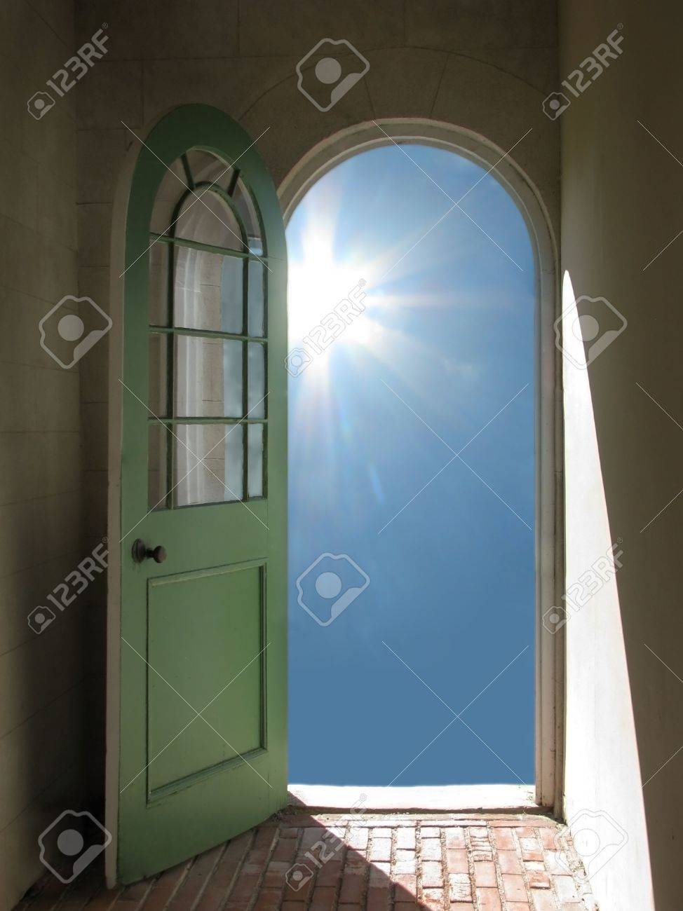 Arched doorway opening on blue sky with sun streaming in Stock Photo - 3088862