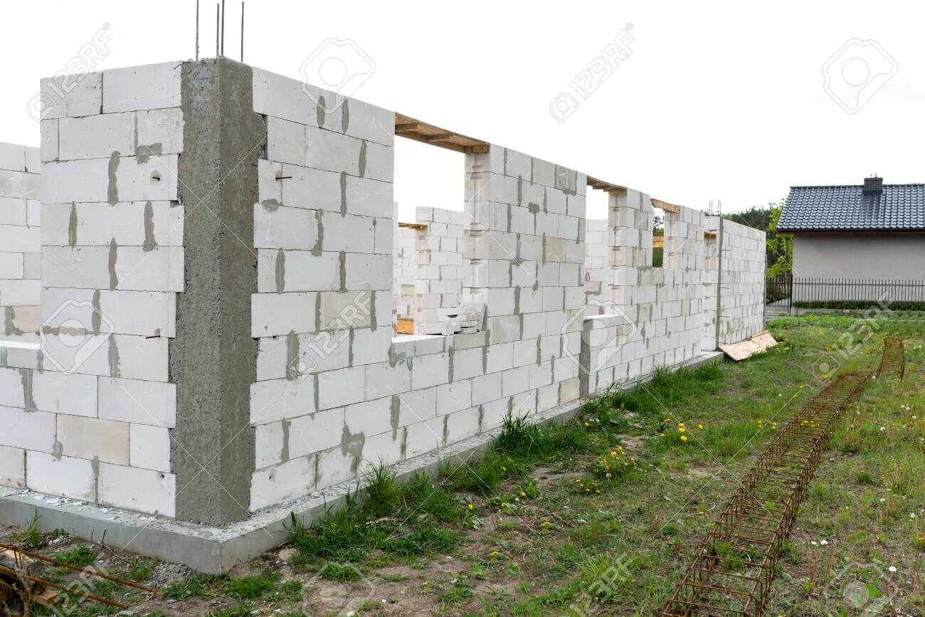 The walls of the house are built with white stones and are in the form of ribbed stones, wooden formwork. - 122399176