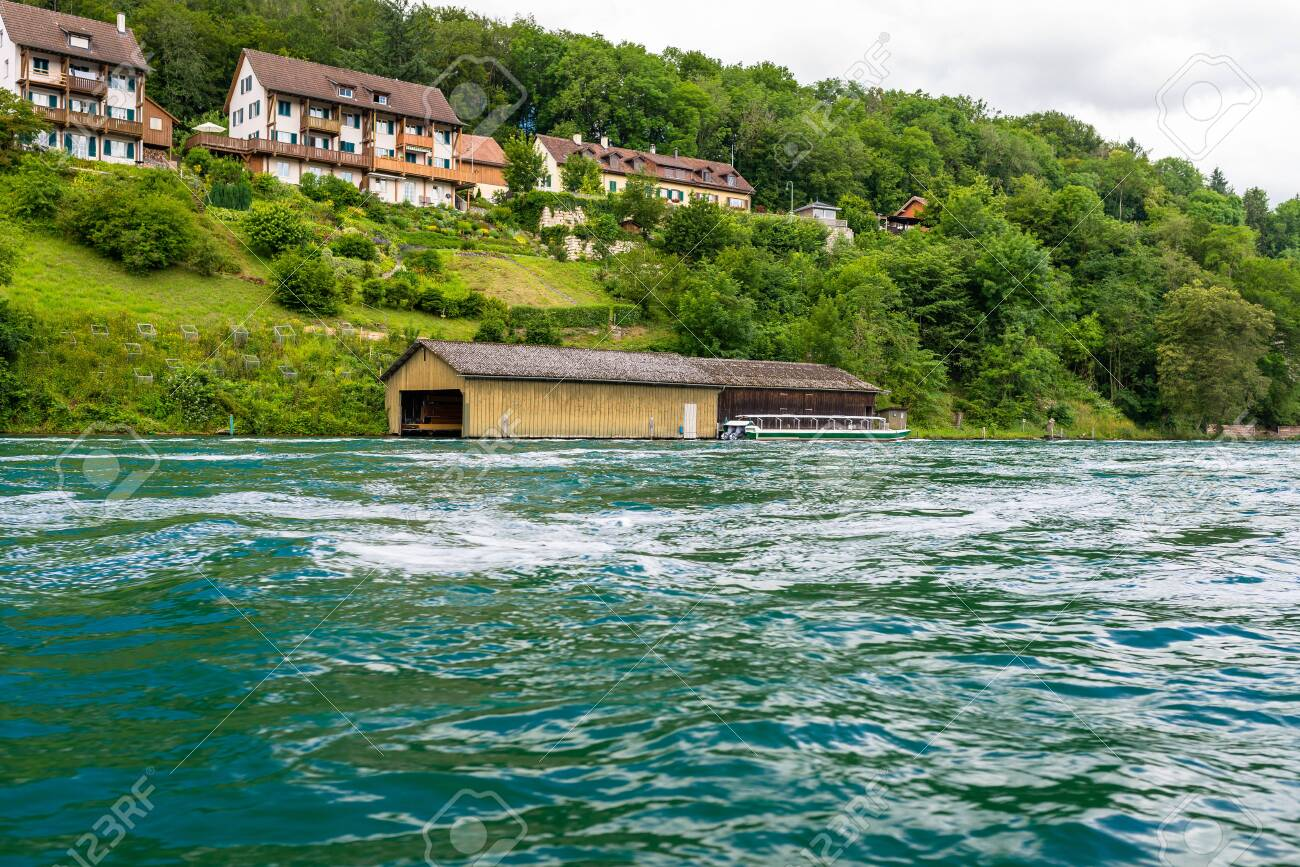 Beautiful view of the Rhine river in turquoise, at the source in Switzerland, just behind the biggest waterfall in Europe. - 128674723