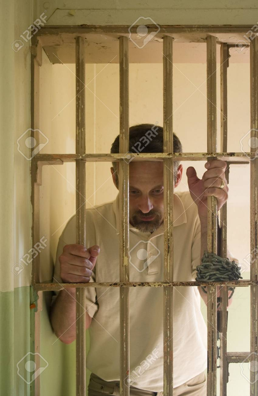 man in prison standing and holding bars Stock Photo - 3691938
