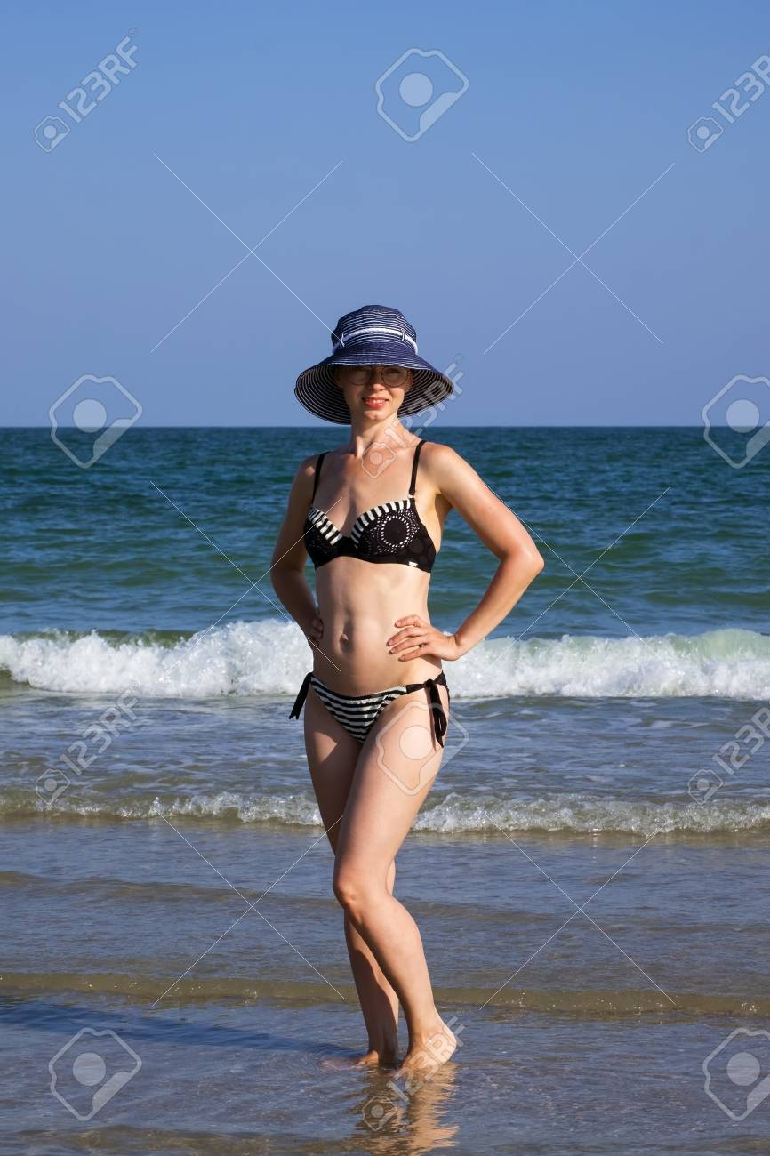 3471332395639 Stock Photo - Young girl in a bathing suit and a striped hat is standing in  the sea with her hands on her waist