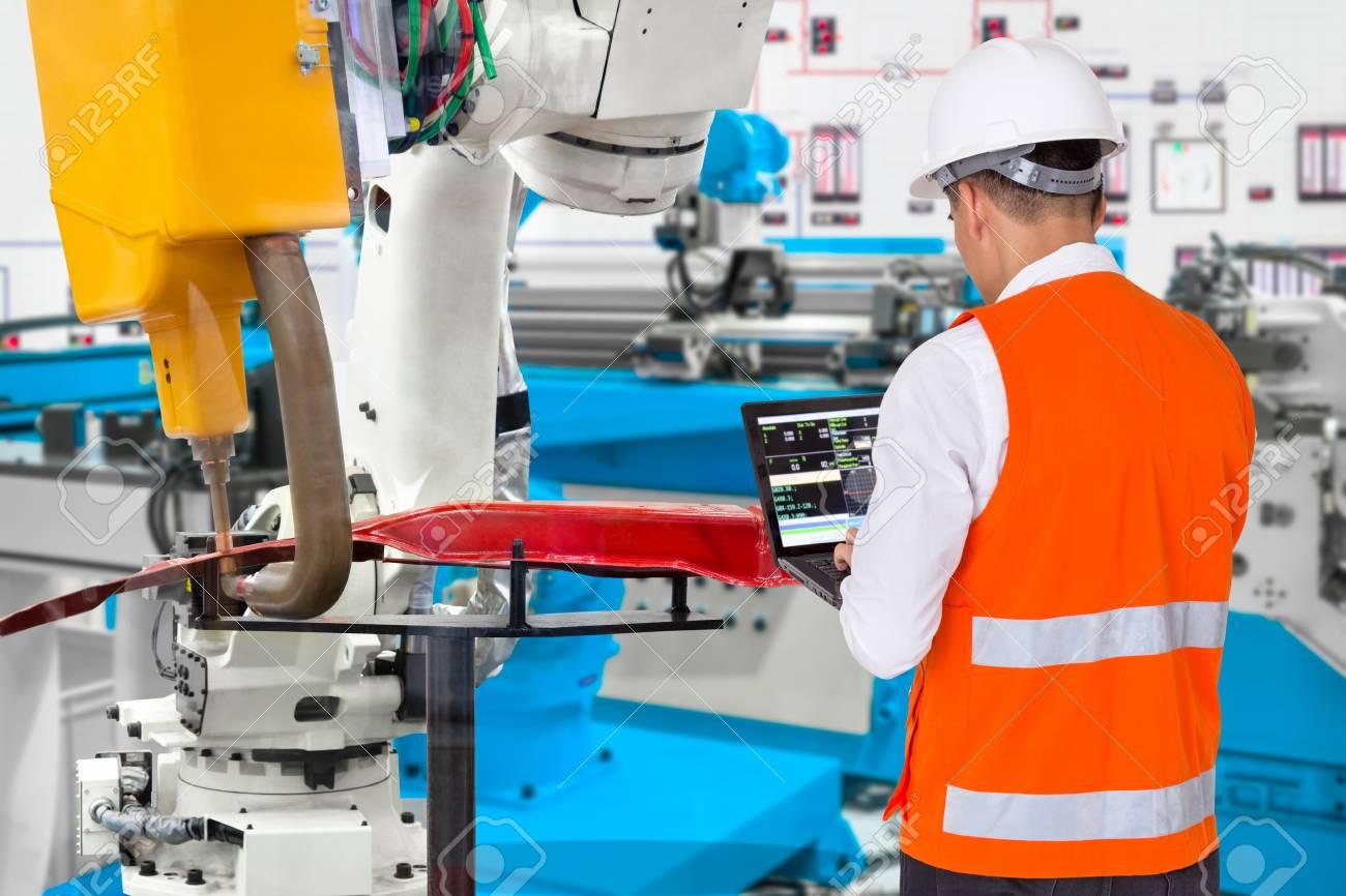 Engineer using laptop computer maintenance robot grip automotive workpiece, Industry 4.0 concept - 120506255