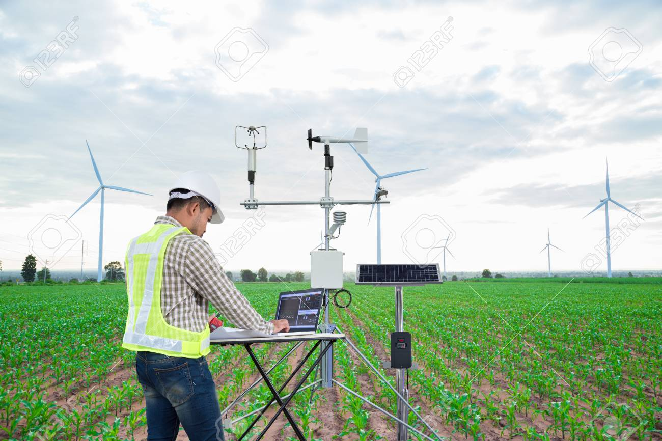 Engineer using tablet computer collect data with meteorological instrument to measure the wind speed, temperature and humidity and solar cell system on corn field background, Smart agriculture technology concept - 120506261