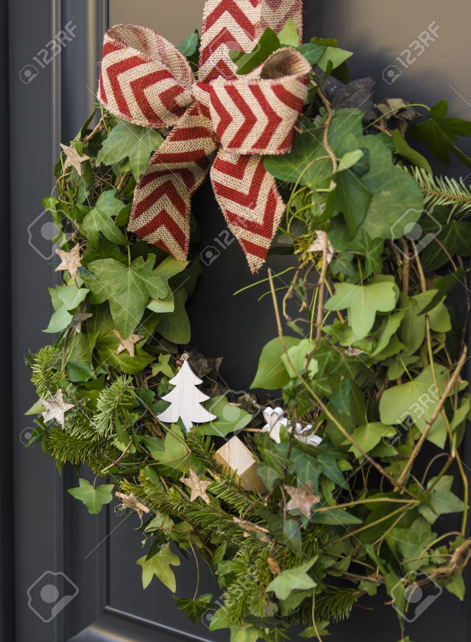 Front Door With A Christmas Wreath Of Ivy And Bows Stock Photo
