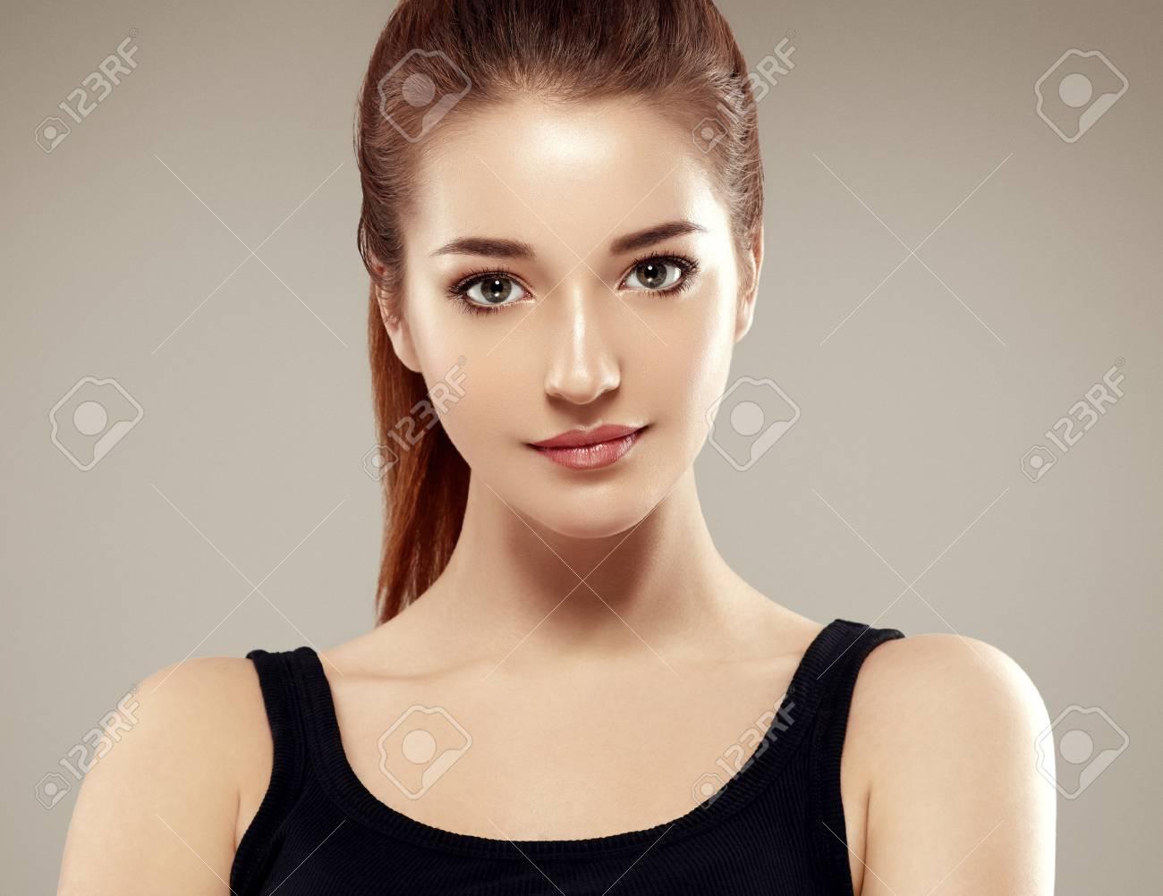 Beautiful woman face close up portrait young. Studio shot. Gray background. - 66203519