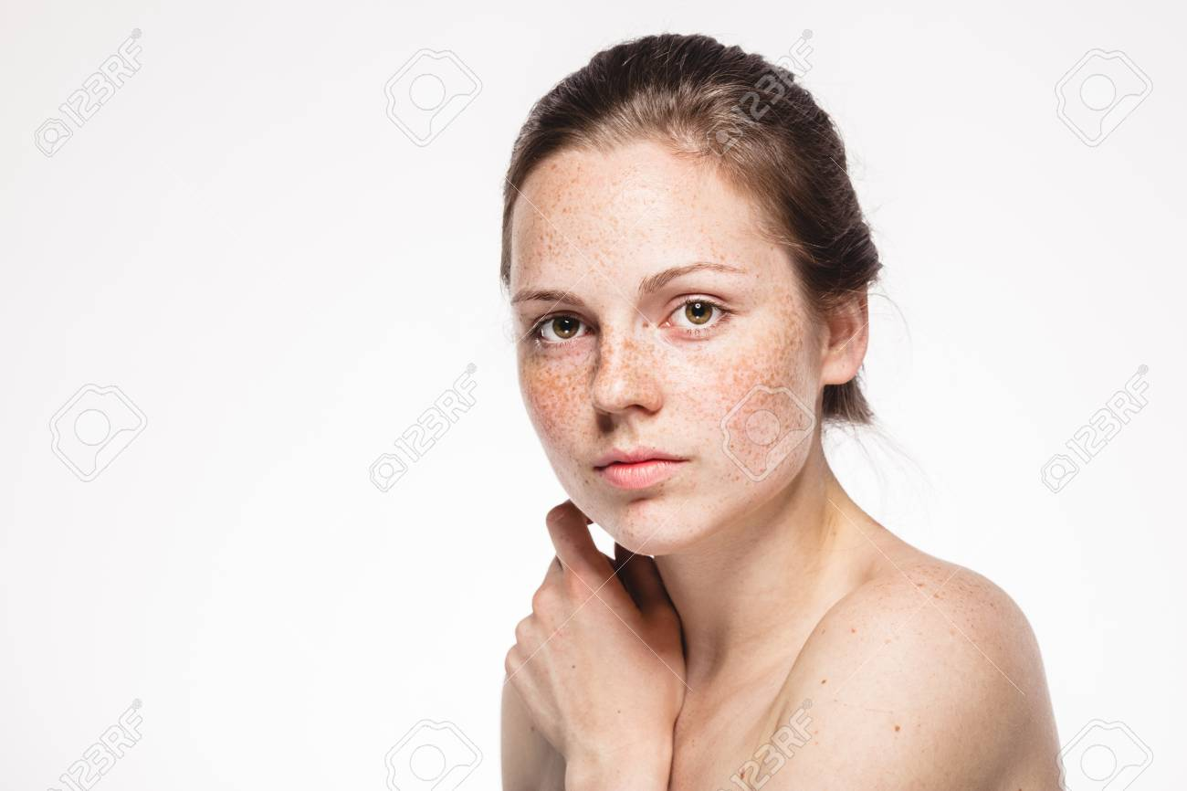Young beautiful freckles woman face portrait with healthy skin. Studio shot. Isolated on white. - 112975603