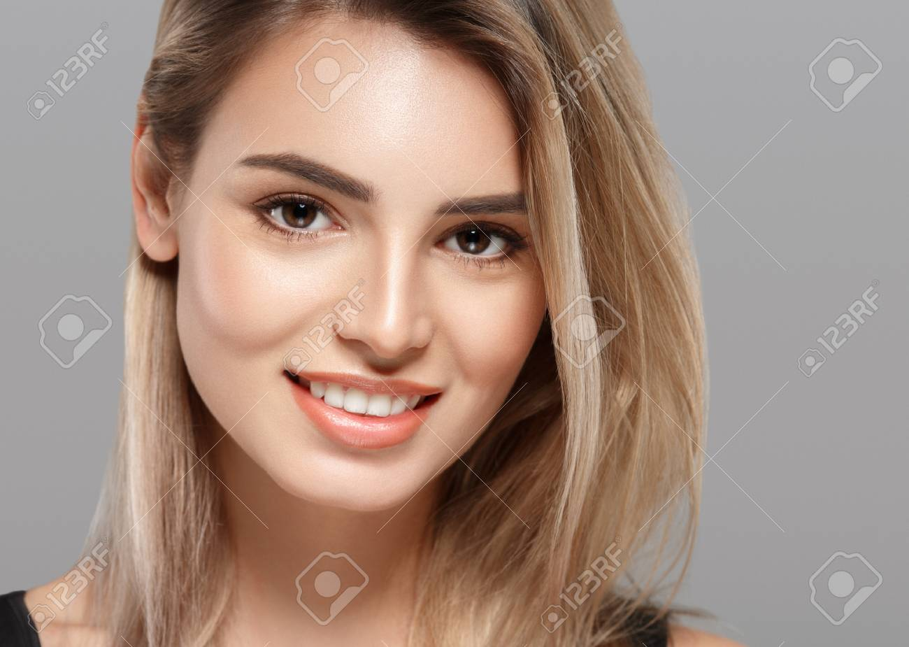 Beautiful young woman portrait smiling posing attractive blond with flying hair on gray background. Studio shot. - 65872850