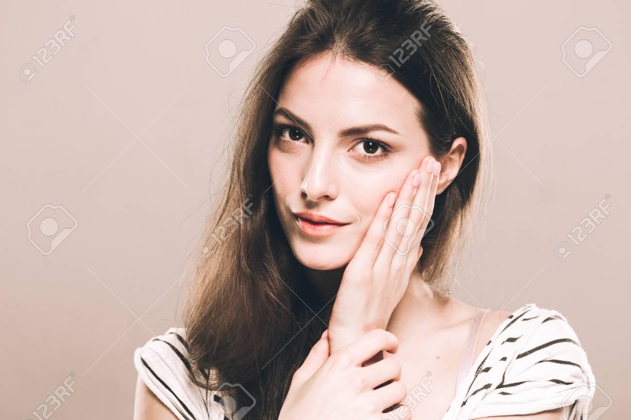 Beautiful young woman portrait touching her chin - 62776758