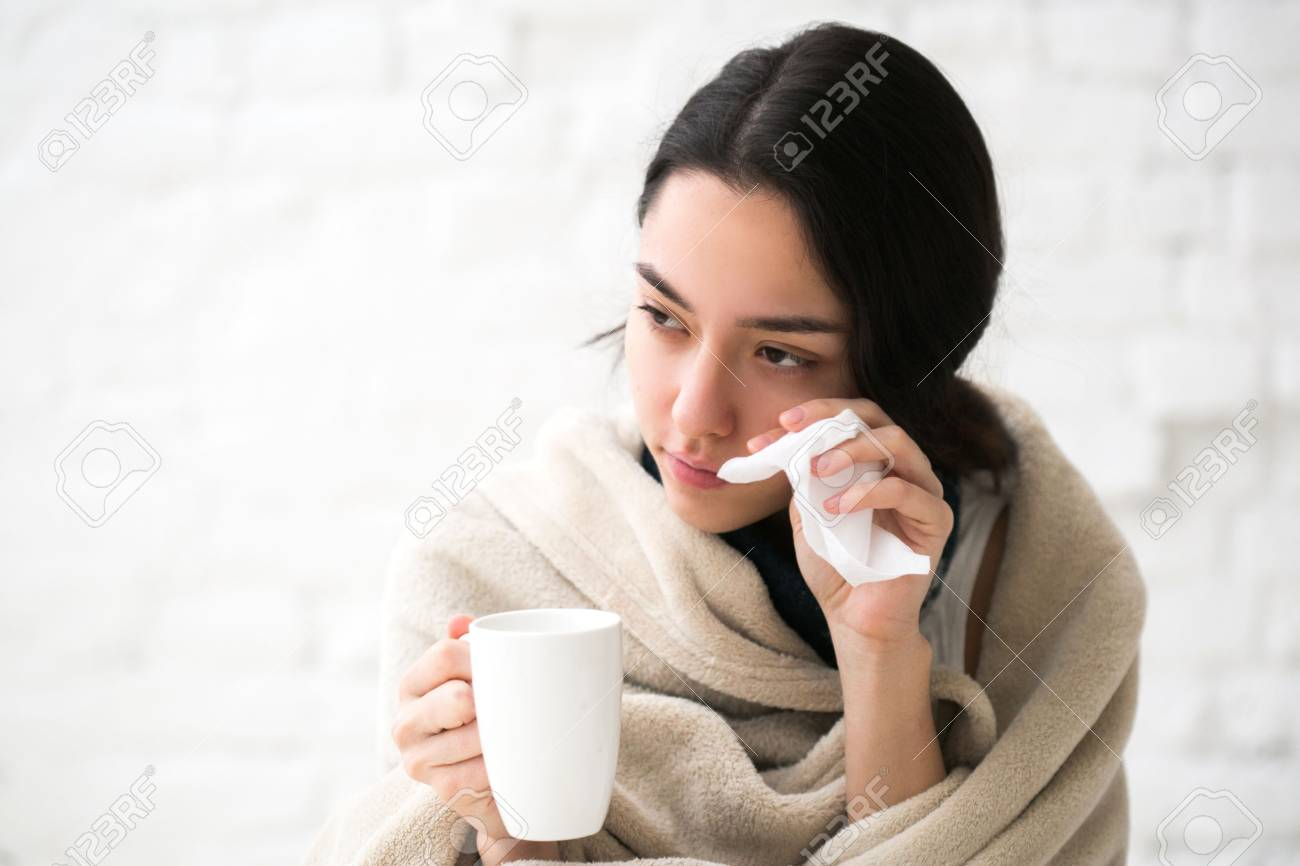 Young woman sick in bed with temperature drinks hot. Indoor shot. - 79345737