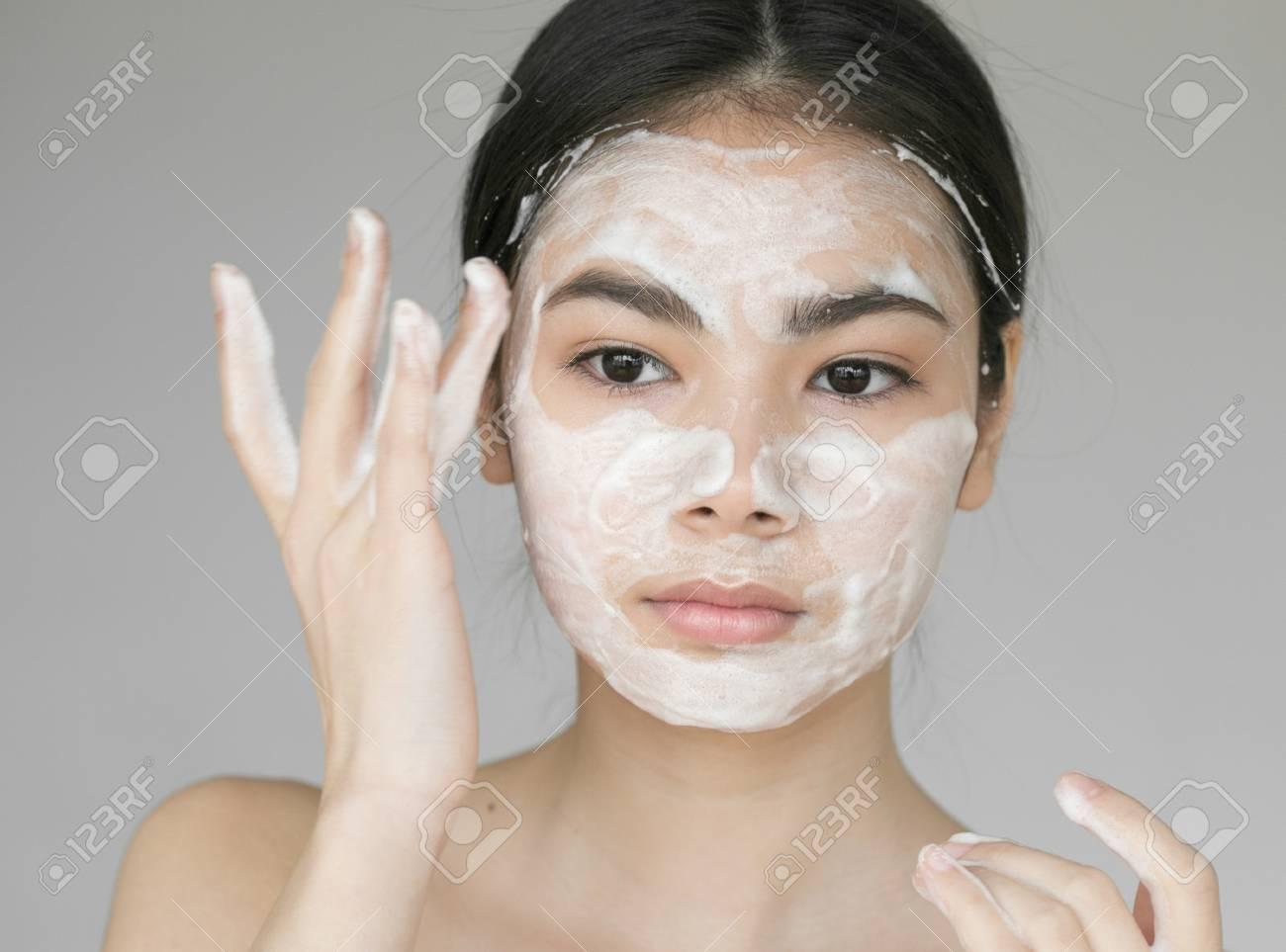 Young beautiful woman washing her face with soap. Studio shot. - 79703793