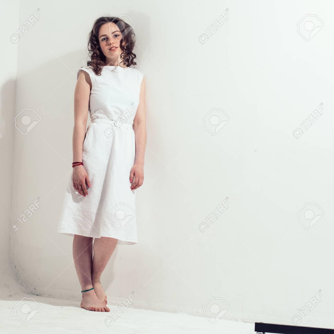 0eae1adad07 Banque d images - Portrait de robe blanche belle fille cheveux bouclés.  Studio tourné Fond gris