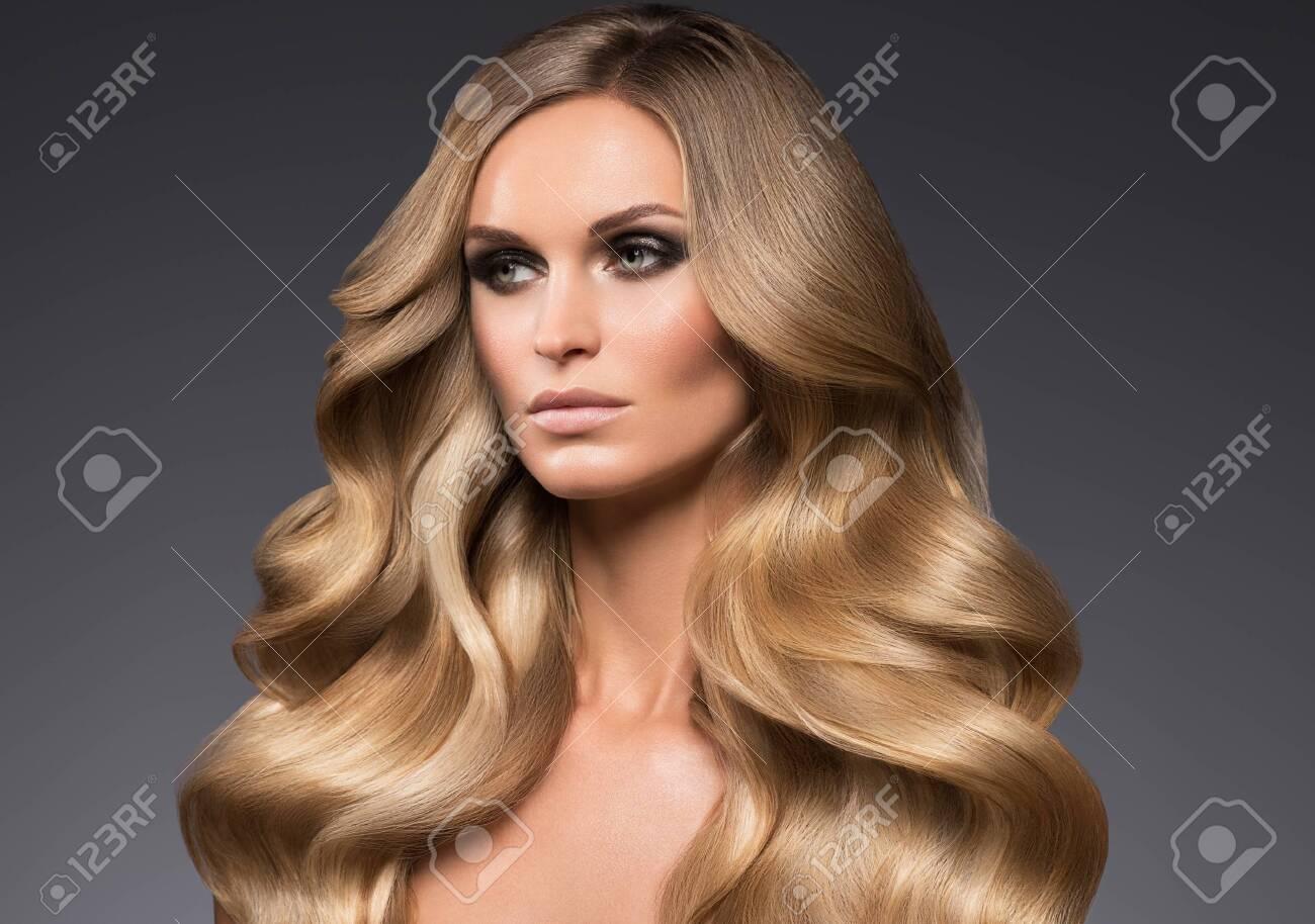 Blond woman long hair curly natural fashion makeup. Studio shot. - 143613621