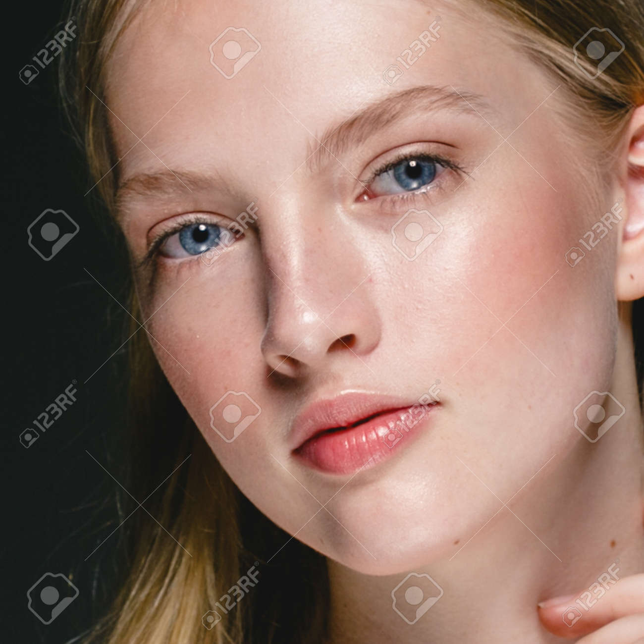 Beautiful Blonde Woman Beauty Model Girl with perfect makeup and hairstyle over black background. - 170272908