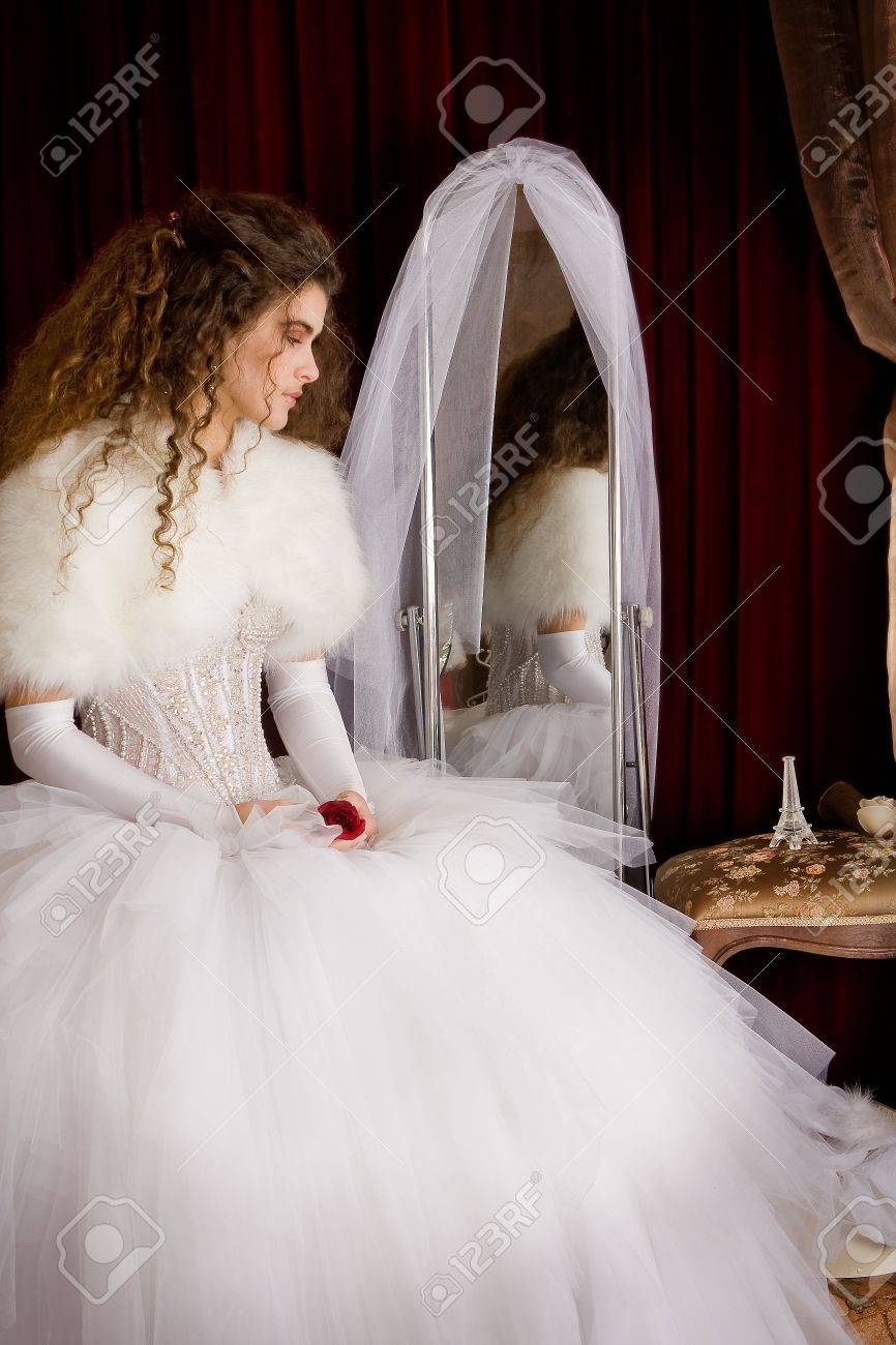 The Bride With Long Brown Curly Hair In A Wedding Dress Sitting