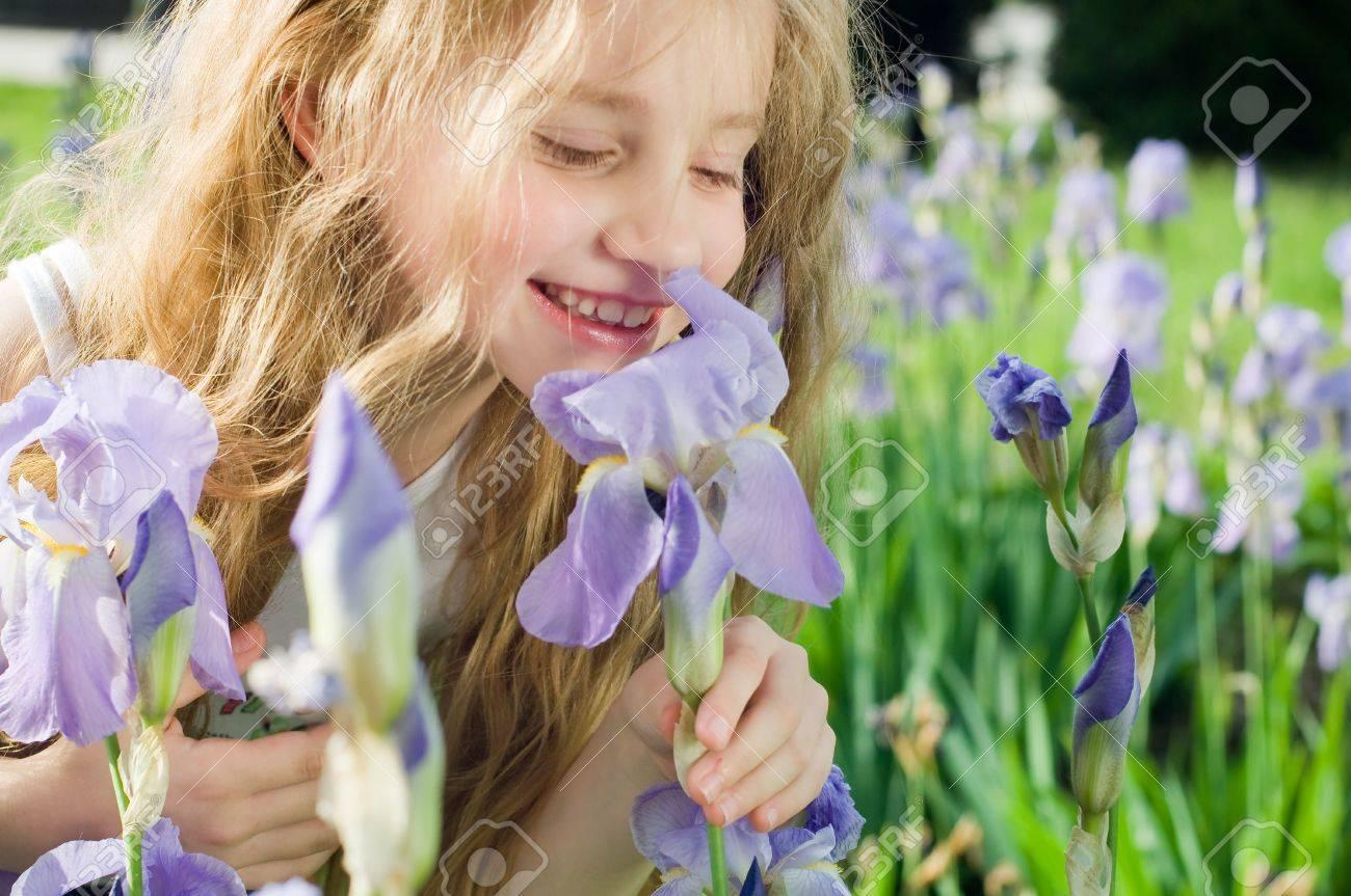 Little girl smelling violet flower outside Stock Photo - 3258114