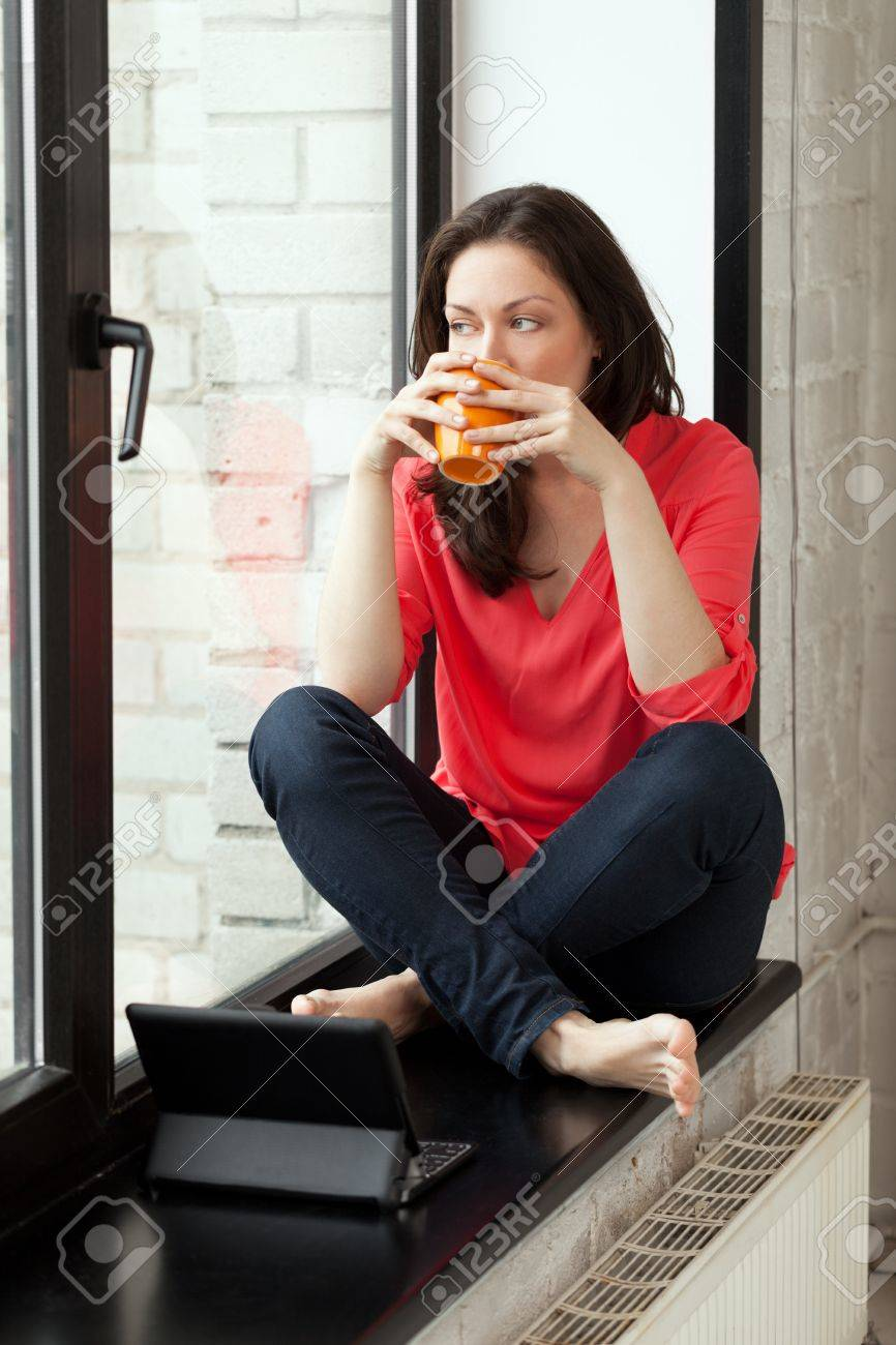 Girl sitting on windowsill with cup of tee and notebook Stock Photo - 14190473