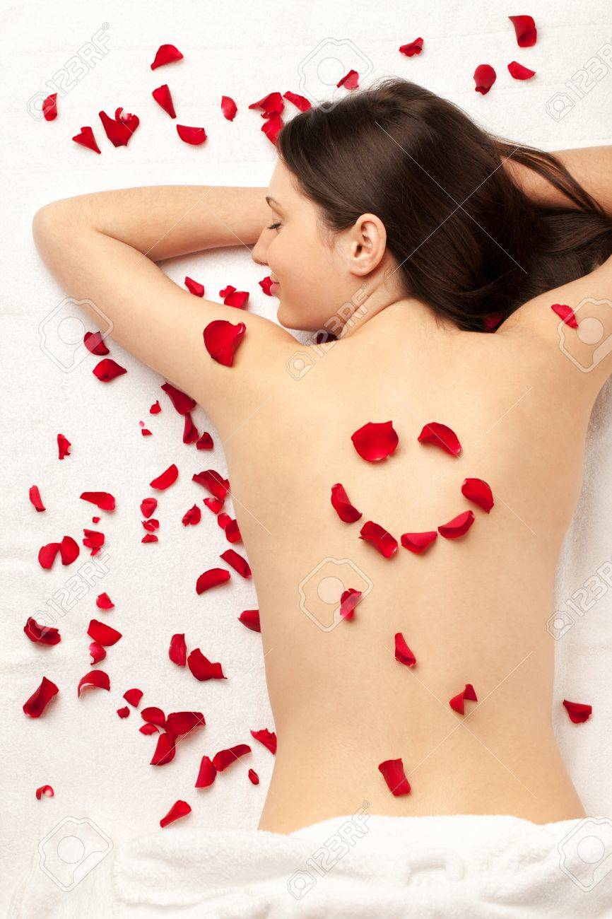 Smiling girl with smiley made of rose petals on back; focus on the face Stock Photo - 14489766