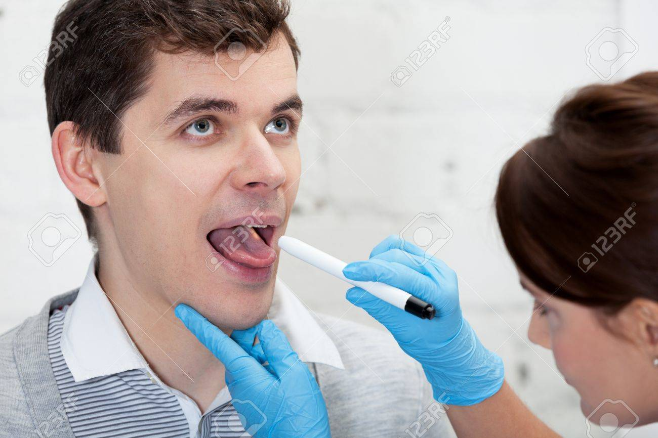Doctor is checking throat of a patient Stock Photo - 16885215